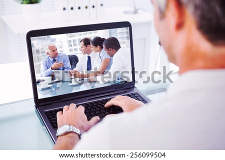 Man with grey hair typing on laptop against group of business people brainstorming together