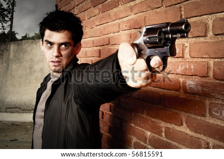 man with gun besides a brick wall