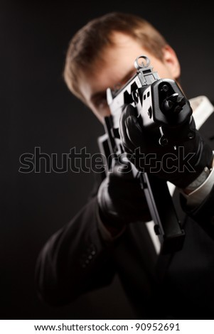 Stock Photo Man with gun over gradient gray. Focused on gun.