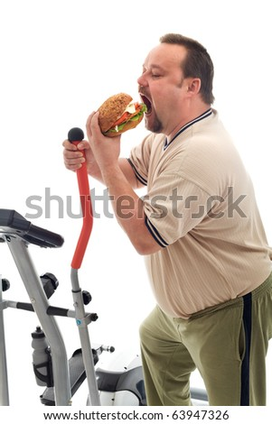 Man with gymnastic trainer device eating a large hamburger - isolated