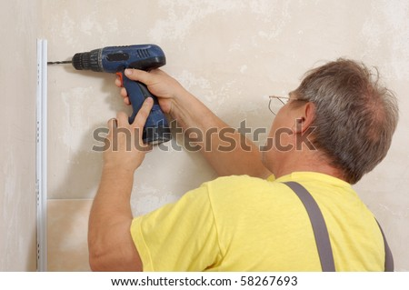 man with hand electric drill make renovation indoor