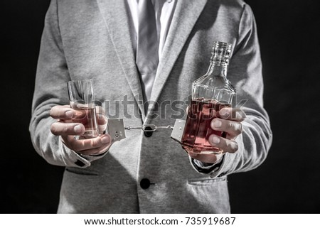 Man with handcuffs, glass and bottle of alcohol drink on black background