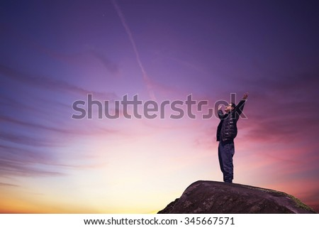 man with hands raised in the sunset concept for religion, worship, prayer and praise