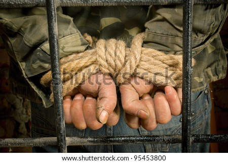 Man with hands tied up with rope behind the bars