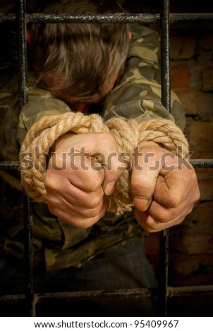 Man with hands tied with rope behind the bars