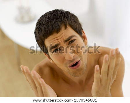 Man with hands up and brow furrowed Stockfoto ©