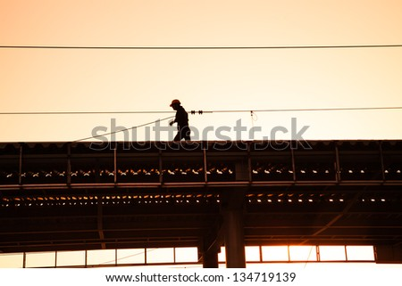 man with hard hat working on the roof near sunset