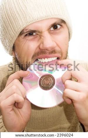 Man with hat holding CD in hands and trying to brake it with his teeth.
