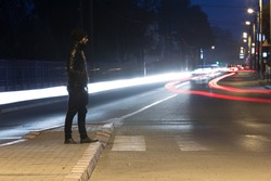 man with hat walking on the street at night with city traffic car trails
