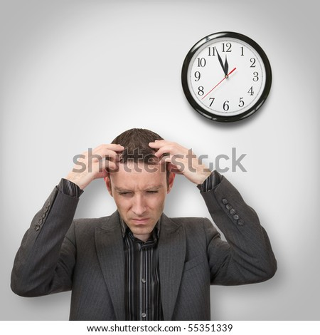 man with headache holding his head and clock behind - stock photo