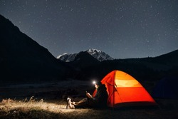 Man with headlamp near glowing orange tent in the mountains under night sky with stars