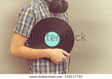 Man with headphones holds vinyl record in his hand. #558117745