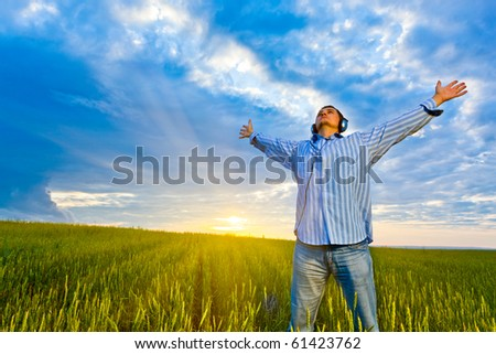 man with headphones standing on field before sunset