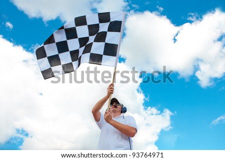 Man with headset holding and waving a checkered flag on a raceway