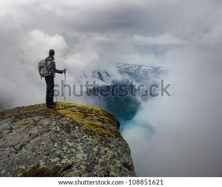 Man with hiking equipment standing on rock's edge