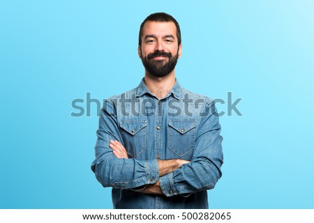 Man with his arms crossed over colorful backgound