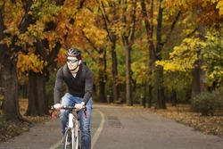 Man with his bike enjoying driving in park in autumn time, with colorful background