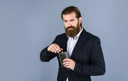 Man with his booze flask. man drinks strong alcohol from iron flask while relaxing. Hip flask for whiskey. vintage gentleman gift shop. Brutal businessman drinking alcohol. copy space.