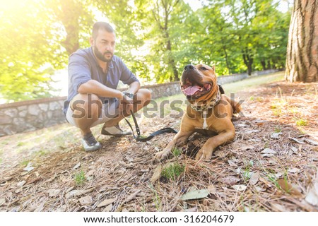 Man with his dog at park. He is looking at his dog standing with open mouth. The main subject is the dog, the man is blurred on the background.