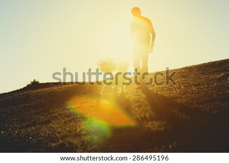 Man with his dog. Dog is sitting on the grass, looking to the man eyes. Back lit.