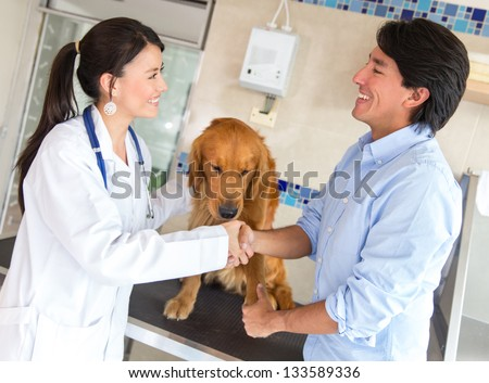 Man with his dog giving handshake to a doctor at the vet
