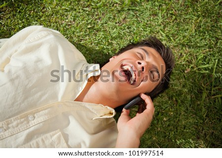 Man with his eyes closed laughing while making a call over the phone as he lies down on the grass