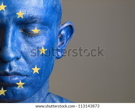 Man with his face painted with the flag of European Union. The man is closed eyes and photographic composition leaves only half of the face. - stock photo
