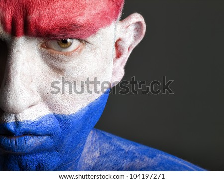 Man with his face painted with the flag of Netherlands.  The man is serious and photographic composition leaves only half of the face.