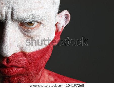 Man with his face painted with the flag of Poland.  The man is serious and photographic composition leaves only half of the face.