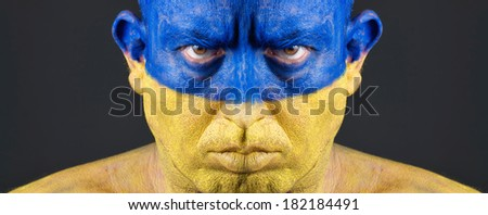 Man with his face painted with the flag of Ukraine.  The man is serious