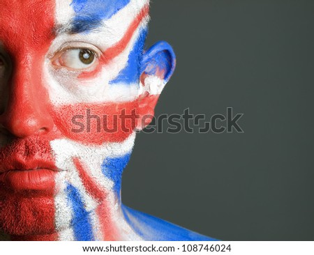 Man with his face painted with the flag of United Kingdom. The man is looking at side and photographic composition leaves only half of the face.