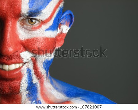Man with his face painted with the flag of United Kingdom. The man is smiling and photographic composition leaves only half of the face.