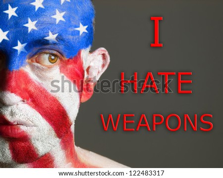 "Man with his face painted with the flag of USA and the text ""I hate weapons"". The man is looking at side"