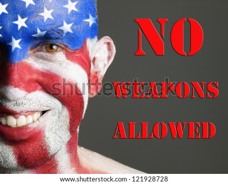 Man with his face painted with the flag of USA. The man is smiling and photographic composition leaves only half of his face. The photo conveys the concept of prohibition of weapons in the U.S.