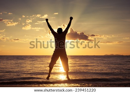 Man with his hands up at the sunset time on the beach #239451220