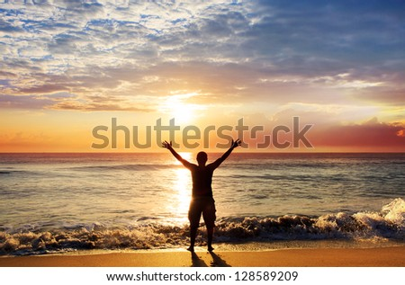 Man with his hands up on the dawn on the beach