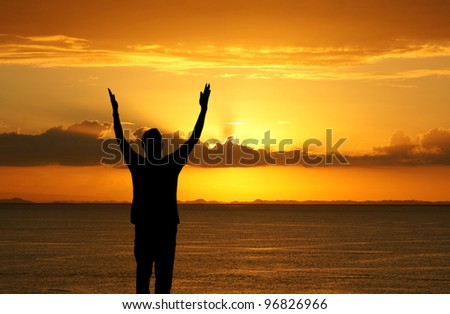 Man with his hands up watching the sun set