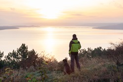 man with his labrador dog admiring orange sunrise over the lake