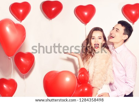 Man with his lovely sweetheart girl dance and have fun at Lover\'s valentine day. Valentine Couple Party. Background red balloons hearts. Love concept. Crazy. Empty copy space for your text.