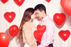 Man with his lovely sweetheart girl kiss at Lover's valentine day. Valentine Couple. Couple kiss and hug. On background red balloons hearts. Love concept. Happy smile girl. Lovers touch foreheads