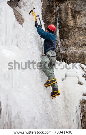 Man with ice axes and crampons climbing on icefall