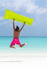 Man with inflatable color green mattress jumping on tropical beach close to sea, enjoying life and having fun on summer vacations