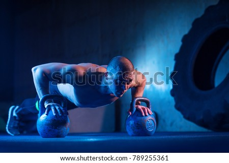 Man with kettlebell weights exercise in the fitness gym. Crossfit training workout. Sports functional training. Weightlifting workout. Sports, cross fit, fitness concept. Strength and motivation. #789255361