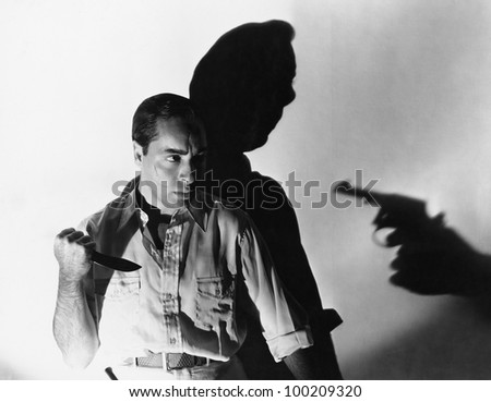 Man with knife at gunpoint - stock photo