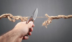 Man with knife cutting frayed rope. Risk