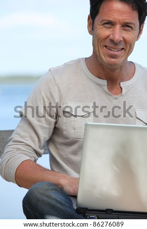 Man with laptop computer sat smiling by water front