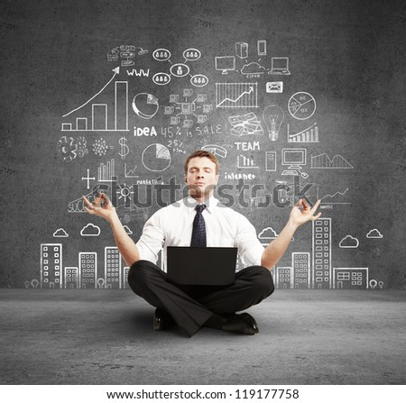 man with laptop meditation and business plan on wall