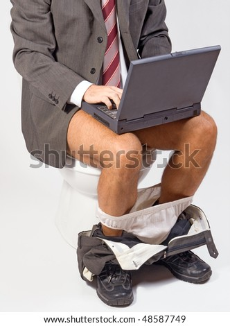 man with laptop sitting on the toilet