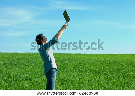 man with laptop standing in a field