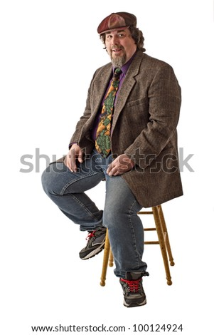 Man with large build sits on stool, dressed casually in tweed cap, jacket and jeans. He smiles and  sits forward with hands on knees. Vertical, isolated on white background, copy space.